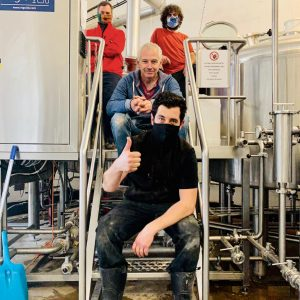Belleville x Mondo Collab – Introducing Hey Neighbour. The Belleville and Mondo brewing teams pose for a photo on the steps within the Belleville Brewery.