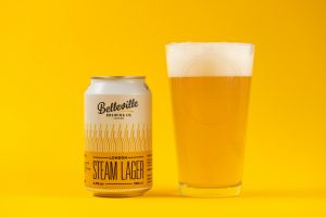 Christmas Beer and Food Pairings. Photograph of a can of Belleville London Stream Lager with a glass of golden coloured beer next to it on a yellow background