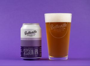 Christmas Beer and Food Pairings. Photograph of a can of Belleville Picnic Session IPA and a glass of amber coloured beer on a purple background