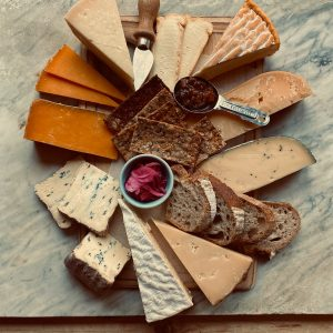 Christmas Beer and Food Pairings. Photograph of a cheeseboard with a selection of crackers, chutneys and assorted cheese