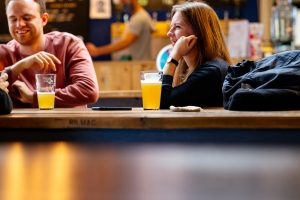 Christmas Beer and Food Pairings. Photograph of a couple drinking beer in the Belleville Taproom