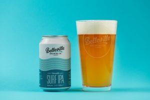 How to drink beer like a pro? Photograph of a blue can of Belleville Brewery Surf IPA with a pint glass of golden beer next to it.