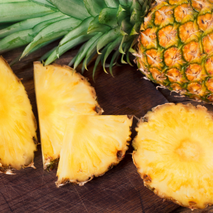 Introducing Philly Buster IPA. A photograph of freshly chopped pineapple on a wooden table