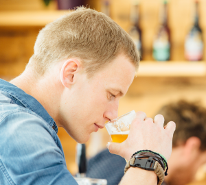 How to drink beer like a pro? Photograph of a young man smelling beer from the glass