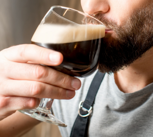 How to drink beer like a pro? Photograph of a bearded man taking a sip of a goblet glass filled with dark beer