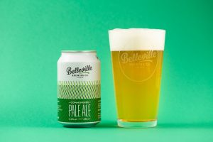Deep Dive Into Commonside Pale Ale. A photograph of Commonside pale ale and a pint of beer on a green background