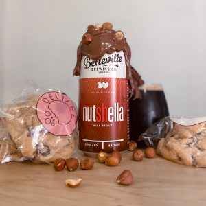Introducing Nutshella Milk Stout. Photograph of a can of nutshella surrounded by chocolate chip cookies and hazelnuts, with molten chocolate dripping from the top of the can and glass