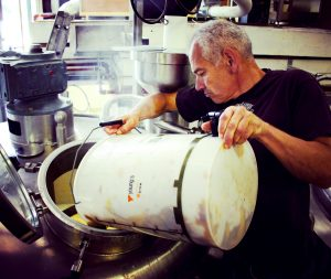 Deep Dive into Commonside Pale Ale. Photograph of Adrian from Belleville pouring a bucket of hops into a tank.