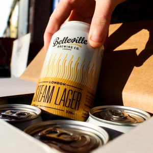 Deep Dive into London Steam Lager. Close up photograph of someone picking a can of London Steam Lager out of a case of beer.